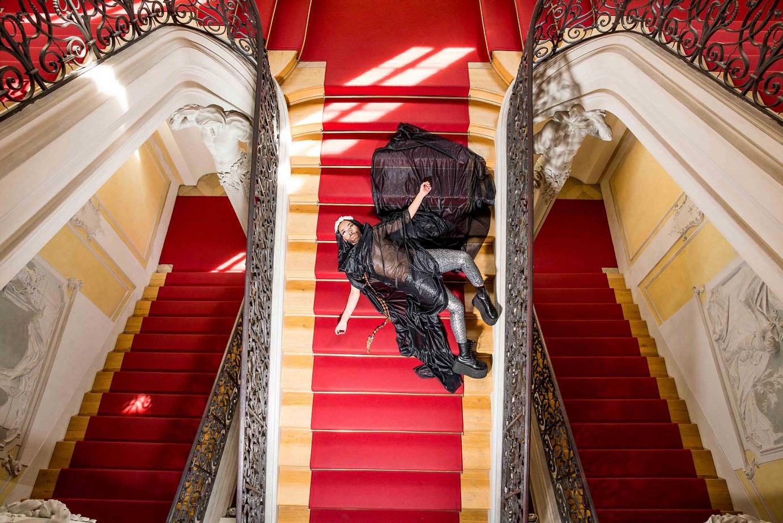 Mann liegt in extraorinärer Kleidung auf Treppe