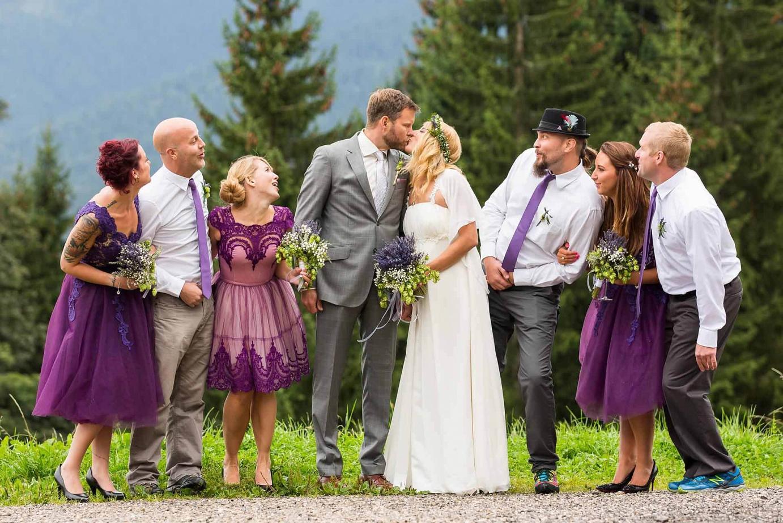Brautpaar küsst sich und Trauzeugen schauen neidisch