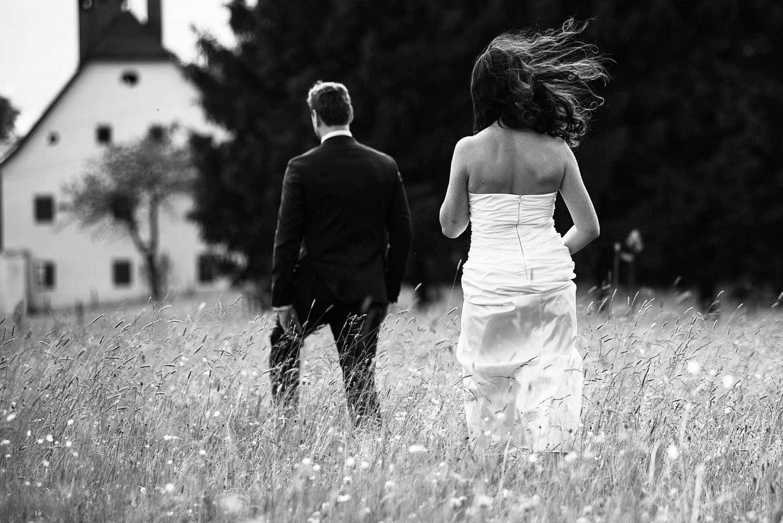 Braut und Bräutigan gehen über eine Wiese
