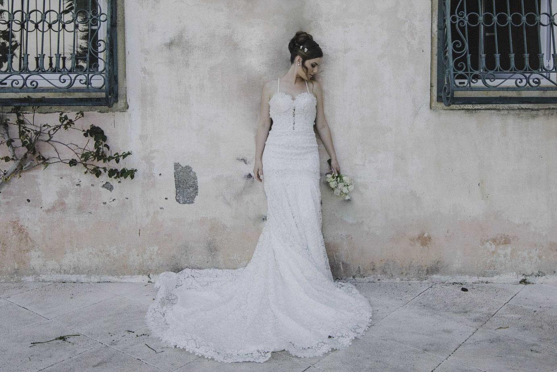 Hochzeitsbraut steht vor einer Wand