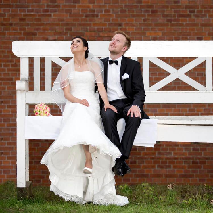 Brautpaar sitzt auf einer übergroßen Bank