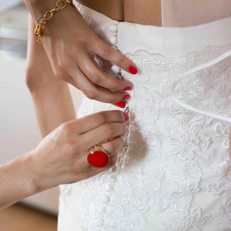 Hände die das Hochzeitskleid schließen