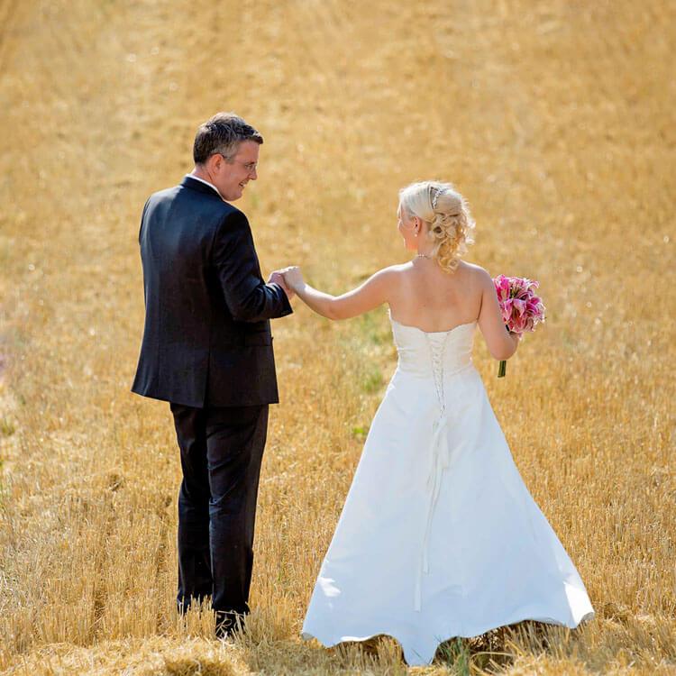 Brautpaar auf einem abgeernteten Weizenfeld