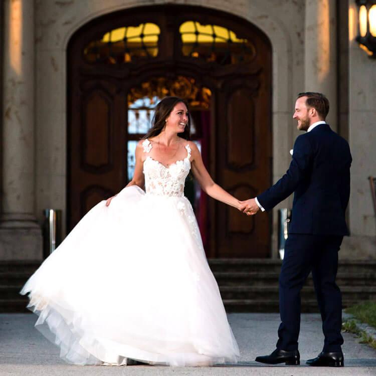 Brautpaar tanzt vor einer Schlosstüre