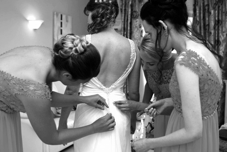 Brautjungfern helfen Brautkleid anzuziehen