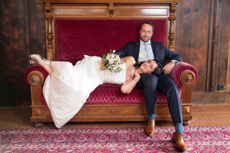 Hochzeitspaar auf einem mondänen alten Sofa.