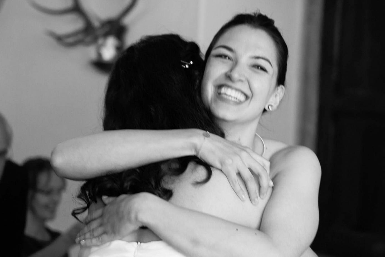 Schwester umarmt die Brau nach der Hochzeit