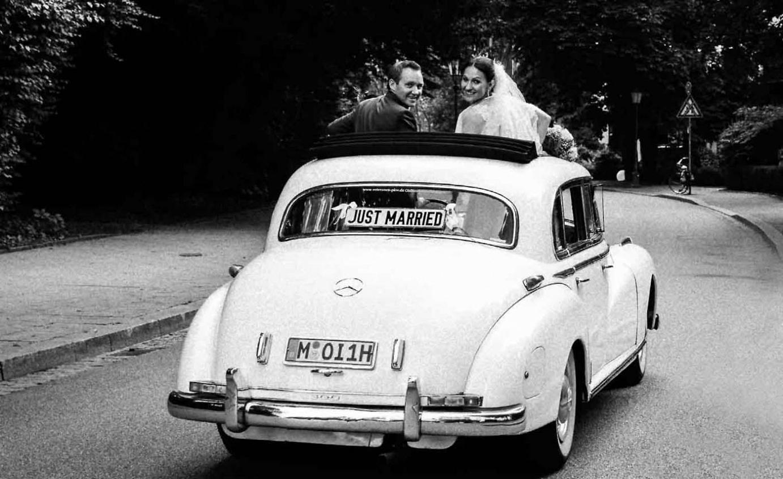 Hochzeitspaar in einem Auto in schwarz-weiss